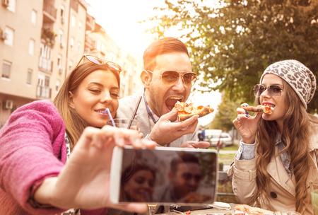 Groep jonge mensen die en een selfie in koffie lachen doen. Zij eten pizza en hebben een geweldige tijd.