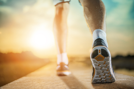 jogging shoes: A person running outdoors on a sunny day.