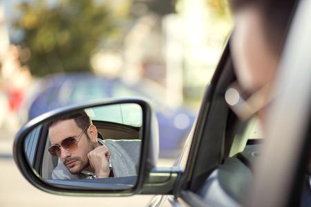modelos hombres: Cerca de una localizaci�n del hombre guapo en su coche, se centran en espejo lateral Foto de archivo