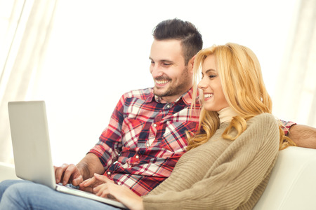 25 30 years women: Young couple browsing internet at home, using laptop and smiling.
