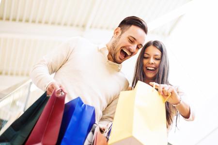 Feliz pareja joven con bolsas de la compra. Foto de archivo