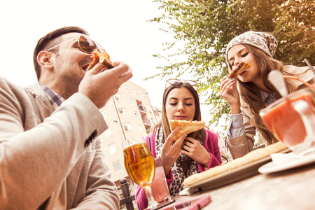 beer after work: Young group of laughing people eating pizza and having fun. Stock Photo