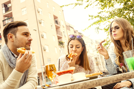 drinks after work: Friends eating pizza and having fun.They are enjoying eating and drinking together.