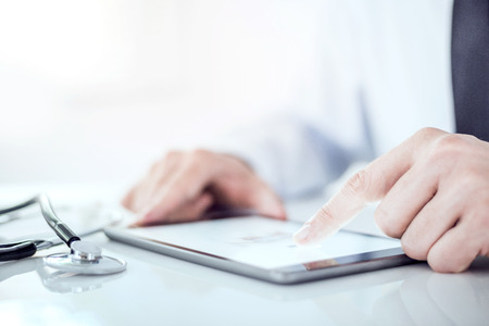 Cropped image of a doctor working on his digital tablet.He is showing digital tablet with blank screen Standard-Bild