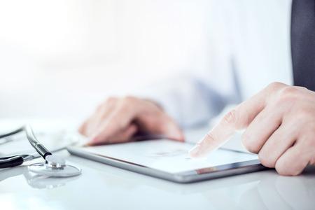 lekarz: Kadrowania obrazu lekarz pracuje nad swoim cyfrowym tablet.He pokazuje cyfrowy tablet z pustego ekranu