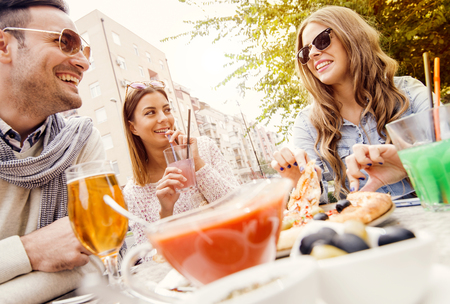 drinks after work: Young group of laughing people eating pizza and having fun.They are enjoying eating and drinking together. Stock Photo