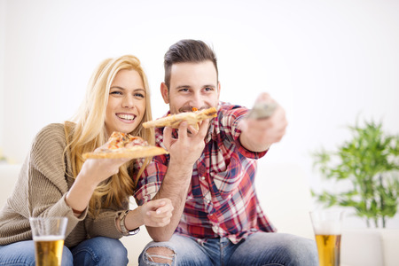 watching movie: Portrait of an happy couple.Cheerful couple relaxing together on couch and watching movie at home.They are laughing and eating pizza and having a great time. Stock Photo