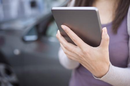 Женщина с помощью смарт-телефона и вызвать страхование автомобиля Фото со стока