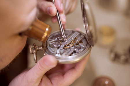 Close up  portrait of a watchmaker at work. He is wearing specialist magnifying glass.Old pocket watch being repaired by watch maker.Selective focus on watch
