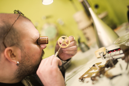 watchmaker: Close up  portrait of a watchmaker at work. He is wearing specialist magnifying glass.Old pocket watch being repaired by watch maker. Stock Photo