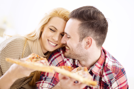 two people only: Portrait of an happy couple.They are laughing and eating pizza and having a great time. Stock Photo