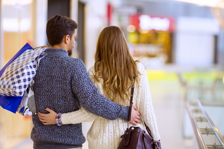 retail place: Happy young couple with shopping bags.Image taken inside a shopping mall.Sale, technology and people concept.