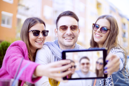Portrait of three friends taking photos with a smartphone.Group of young people laughing and doing a selfie in cafe. Stock Photo