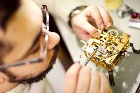 watchmaker: Close up  portrait of a watchmaker at work. He is wearing specialist magnifying glass.Old pocket watch being repaired by watch maker.Selective focus on watch.