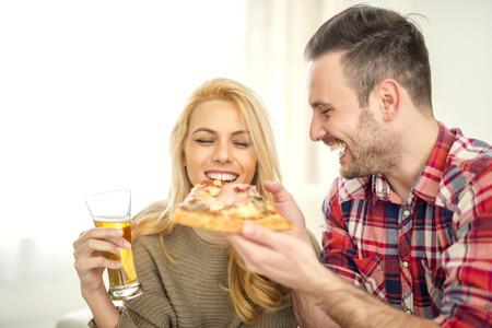 Casal relaxando em casa e comer pizza, tendo um grande momento.