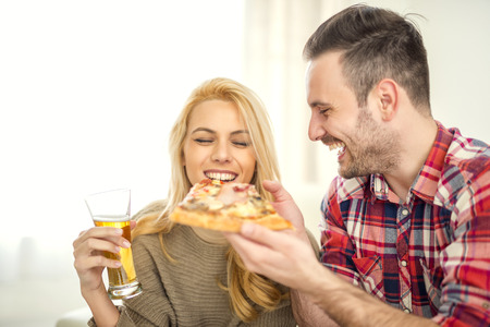 Couple relaxing at home and eating pizza,having a great time. Banque d'images