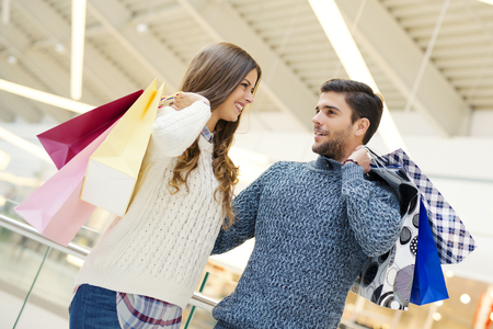 retail place: Sale, technology and people concept - happy young couple with shopping bags.Image taken inside a shopping mall. Stock Photo