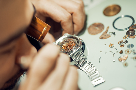 watchmaker: A watchmaker or repair man in action,viewing very closely a watch. Stock Photo