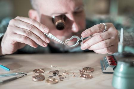 Cerca de retrato de un relojero en el reloj de bolsillo work.Old siendo reparado por el fabricante de relojes.