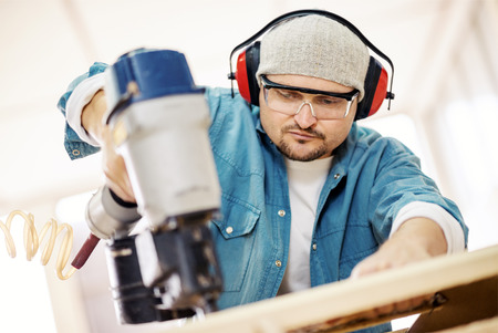 homeowner: Carpenter at work.Safety-conscious contractor or homeowner working with nail gun Stock Photo