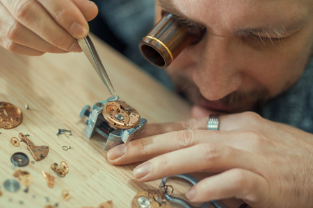 watchmaker: Close up portrait of a watchmaker at work.Old pocket watch being repaired by watch maker.