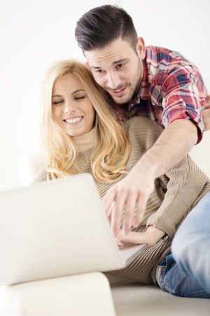 Cheerful couple relaxing together on couch surfing internet on laptop at home.They are looking at laptop and smiling. Stock Photo