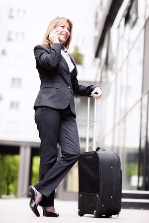 only mid adult women: Businesswoman traveling.Front view of a traveler woman walking and using a smart phone in an airport.
