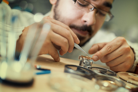 watchmaker: Close up portrait of a watchmaker at work.He is wearing specialist magnifying glass.