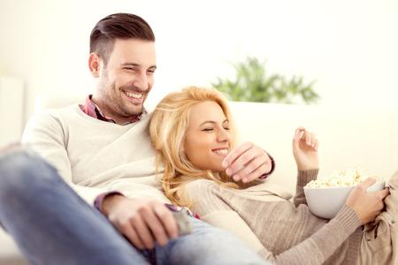 快樂的年輕夫婦在家中爆米花看電視躺在沙發上。他們都笑了,看電影或電視。 版權商用圖片