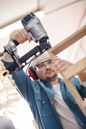 homeowner: Safety-conscious contractor or homeowner working with nail gun Stock Photo