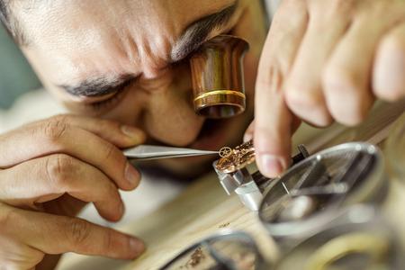 Feche acima do retrato de um relojoeiro em work.A relojoeiro ou homem de reparação em ação, vendo de perto um relógio suíço.