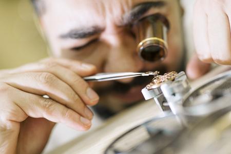 仕事で時計職人の肖像画を間近します。彼は専門家の虫眼鏡を着ています。古い懐中時計の時計メーカーによって修復されています。