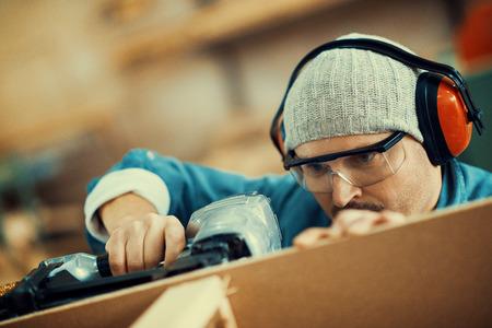 安全意識的承包商或房主用釘槍工作。 版權商用圖片