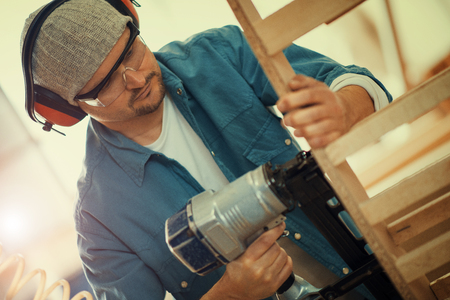 homeowner: Carpenter at work.Safety-conscious contractor or homeowner working with nail gun.