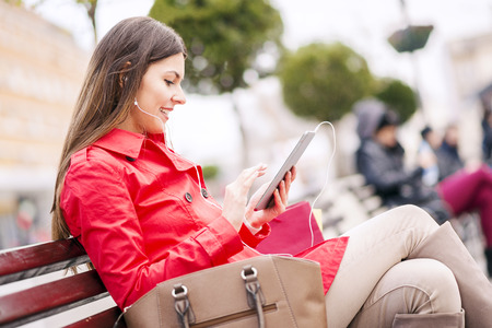 handsfree device: Moment for enjoying .Happy girl listening music on headphones and enjoying in the city. Stock Photo