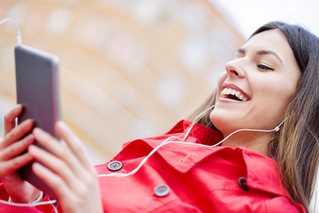 Moment for enjoying .Happy girl listening music on headphones and enjoying in the city. Stock Photo