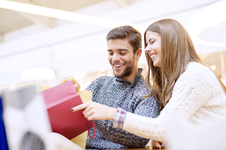 Happy young couple with shopping bags.Image taken inside a shopping mall. Stock Photo