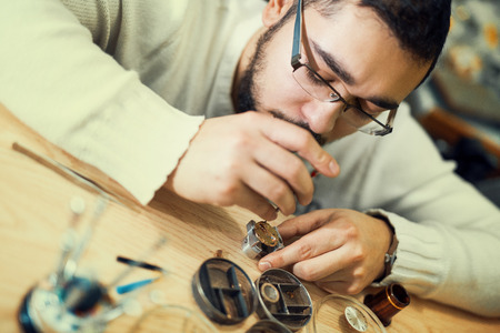 watchmaker: Close up portrait of a watchmaker at work.A watchmaker or repair man in action,viewing very closely.
