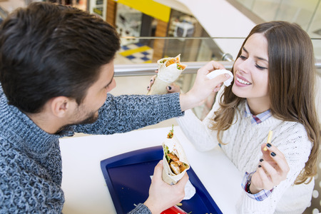 shopping binge: Couple looking at each other while eating fast food.Image taken inside a shopping mall.