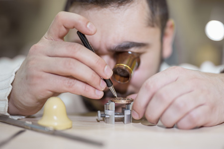 watchmaker: Close up portrait of a watchmaker at work. He is wearing specialist magnifying glass. Stock Photo