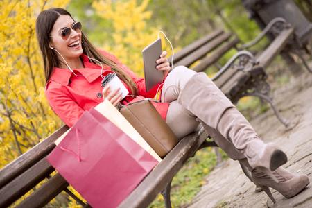 Gelukkig meisje luisteren muziek op de koptelefoon en genieten in de park.She is op zoek erg blij na het winkelen.
