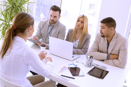 Grupo de hombres de negocios que tienen interview.They trabajo se están comunicando con la candidata femenina.