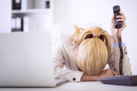 Empresaria frustrada en el escritorio en office.Having un dolor de cabeza después de trabajar muy duro.