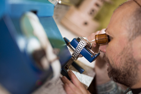 watchmaker: Close up portrait of a watchmaker at work.He is working on vibrograph. Stock Photo