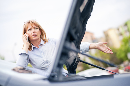 car trouble: Woman with car trouble in the middle of the street, after car breakdown. She is on the phone, calling for assistance.She is waiting for the technician to arrive. Stock Photo