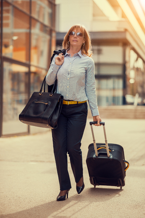 Front view of a traveler woman walking in an airport Stock Photo