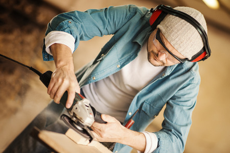 orbital: Carpenter working on a project in his workshop.A man sands piece of wood with an orbital power sander. Stock Photo