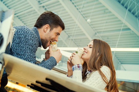 eating fast food: Couple looking at each other while eating fast food.They are having fun in fast food restaurant.