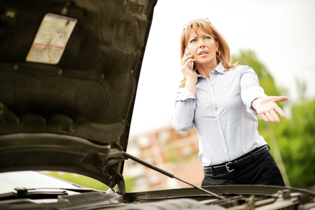 one mature woman only: Woman with car trouble in the middle of the street, after car breakdown. She is on the phone, calling for assistance.