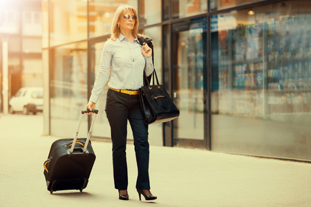 Business travel.Front view of a traveler woman standing and using a smart phone in an airport. Stock Photo